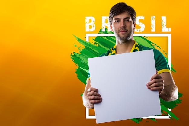 Feliz hombre brasileño, aficionado al fútbol con cartel en blanco
