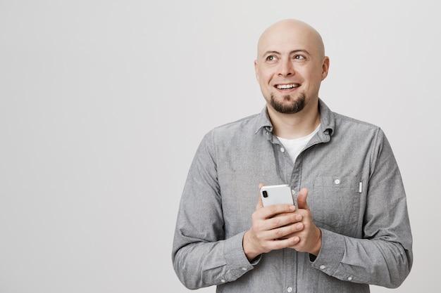 Feliz hombre calvo pensativo mirar hacia otro lado, sonriendo como usando un teléfono móvil