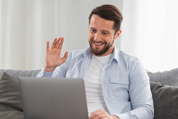 Feliz hombre caucásico usa computadora portátil para videollamadas mientras está sentado en el sofá en casa, sonriente hombre caucásico charlando con amigos o familiares a través de videoconferencia en las redes sociales, gesto de saludo