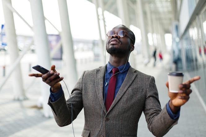 Feliz hombre de negocios afroamericano baila mientras escucha la música