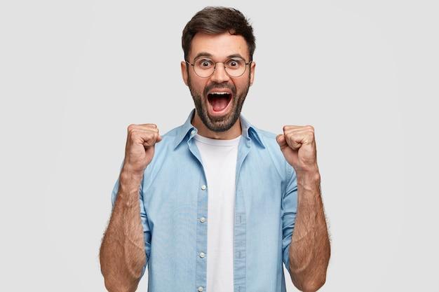 Feliz hombre exitoso aprieta los puños, grita de felicidad, celebra el triunfo