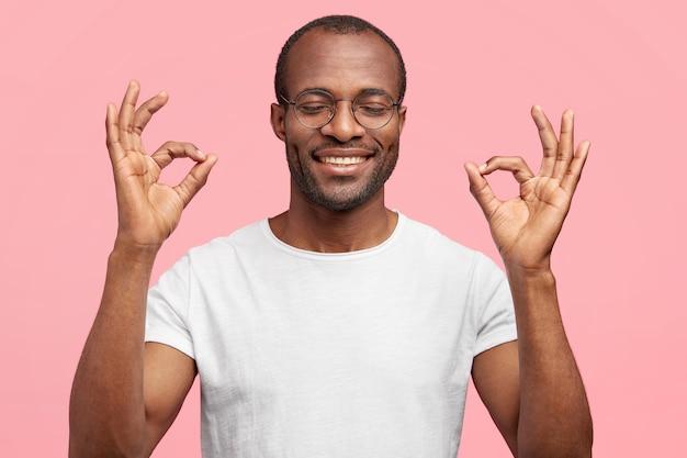 Feliz hombre de mediana edad con amplia sonrisa dentuda, muestra un gesto aceptable, cierra los ojos con placer, vestido informalmente, aislado en la pared rosa