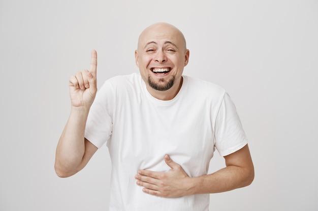 Feliz hombre de mediana edad calvo riendo sobre copyspace, apuntando hacia arriba como risa