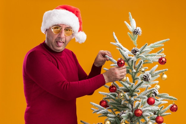 Feliz hombre de mediana edad vestido con gorro de papá noel de navidad en cuello alto rojo oscuro y gafas amarillas sacando la lengua decorando el árbol de navidad de pie sobre la pared naranja