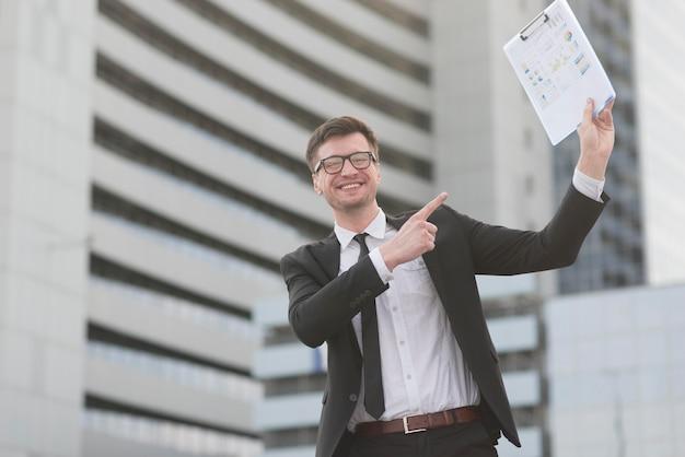 Feliz hombre moderno apuntando al portapapeles