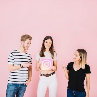 Feliz hombre y mujer apuntando a su amigo con icono de instagram