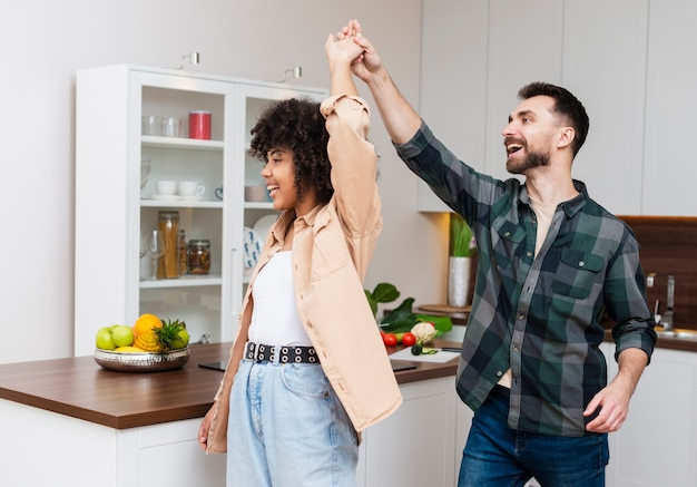 Feliz hombre y mujer bailando en la cocina