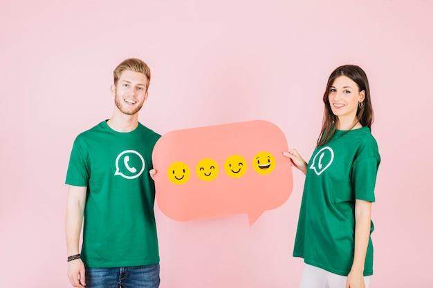 Feliz hombre y mujer con burbujas de discurso con varios tipos de emociones