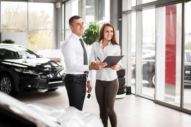 Feliz hombre y mujer cerrar trato de coche