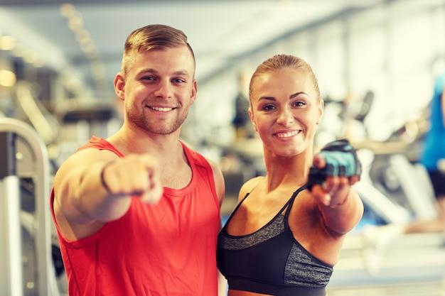 Feliz hombre y mujer dedo señalador en el gimnasio