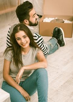 Feliz hombre y mujer sentados en el suelo cansados preparándose para trasladarse a un nuevo apartamento