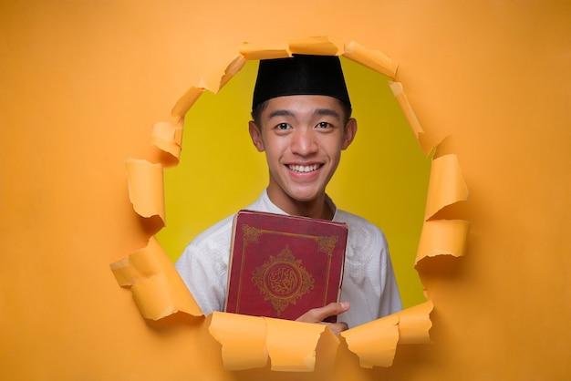 Feliz hombre musulmán asiático sosteniendo el sagrado corán, vestido con tela musulmana con gorra, posa a través del agujero de papel amarillo roto, leyendo el sagrado corán en ramadán kareem