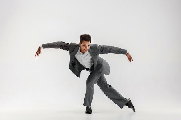 Feliz hombre de negocios bailando en movimiento aislado sobre fondo blanco de estudio. flexibilidad y gracia en los negocios. concepto de emociones humanas. oficina, éxito, profesional, felicidad, conceptos de expresión