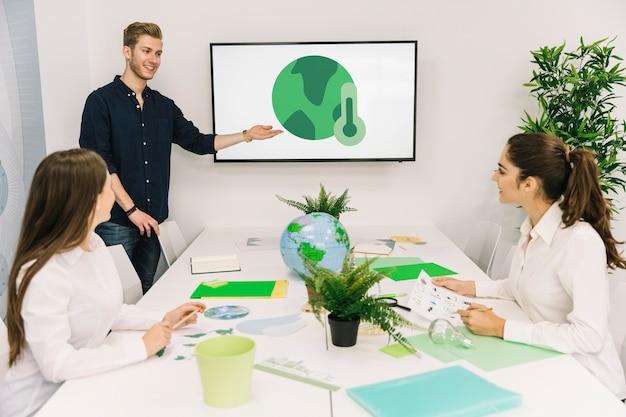 Feliz hombre de negocios dando presentación sobre calentamiento global a sus colegas femeninos