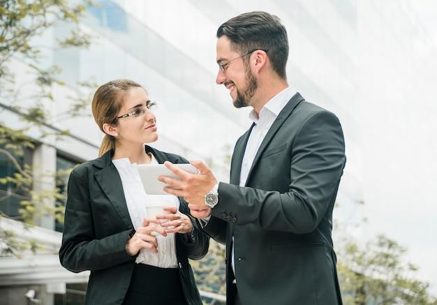 Feliz hombre de negocios y empresaria de pie fuera de la oficina mirando el uno al otro