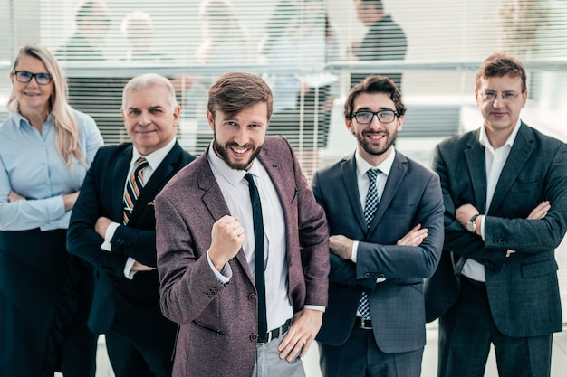 Feliz hombre de negocios y un grupo de destacados expertos parados juntos