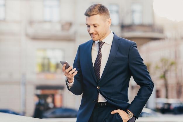Feliz hombre de negocios mantiene la mano en el bolsillo vistiendo traje formal y reloj de pulsera y utilizando teléfonos inteligentes