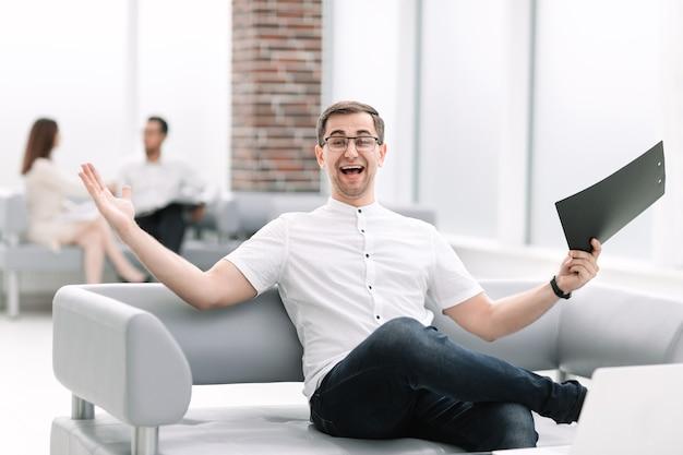 Feliz hombre de negocios sentado en el vestíbulo del banco