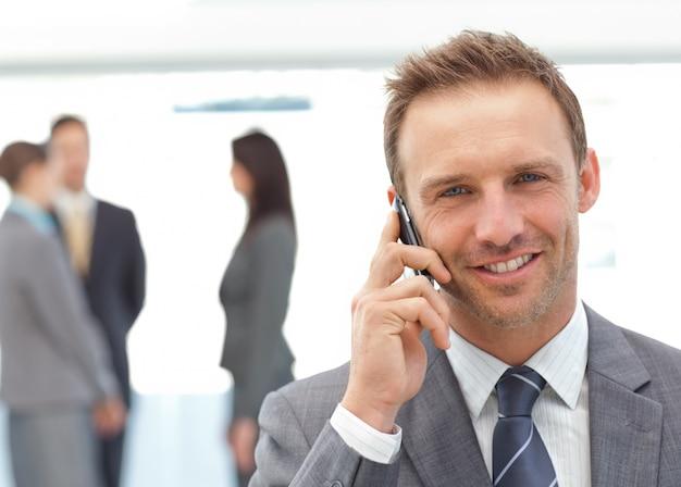 Feliz hombre de negocios en el teléfono mientras su equipo trabaja