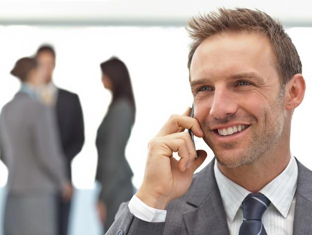 Feliz hombre de negocios en el teléfono durante una reunión