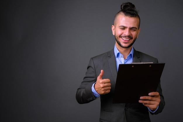 Feliz hombre de negocios turco barbudo en traje leyendo en el portapapeles y dando pulgar hacia arriba