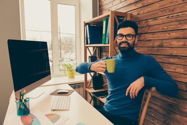 Feliz hombre de negocios en vasos sosteniendo una taza de café y sonriendo
