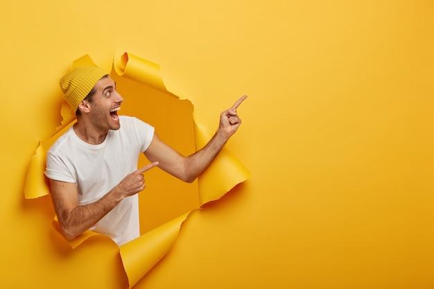 Feliz hombre satisfecho señala en la esquina superior derecha, se encuentra medio girado, muestra una gran oferta comercial, posa en un agujero rasgado