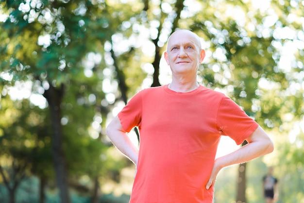 Feliz hombre senior pensativo de pie en el parque