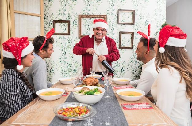 Feliz hombre viejo abriendo botella de vino en mesa festiva