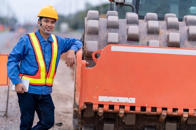 Feliz ingeniero civil de pie lateral suelo vibratorio amarillo en el sitio de construcción de carreteras