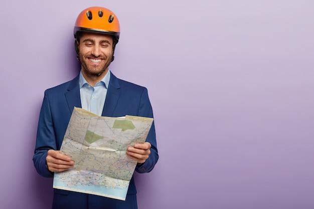 Feliz ingeniero constructor examina el plano del sitio de construcción, tiene expresión de cara alegre, usa casco, traje formal
