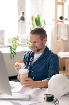 Feliz ingeniero maduro sentado junto al escritorio delante del monitor de la computadora y mirando divertido cupcake en su mano antes de comerlo