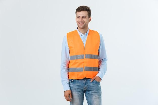 Feliz ingeniero sonriendo y de pie con confianza, chico vestido con camisa caro y jeans con chaleco naranja, aislado sobre fondo blanco.