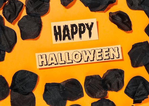 Feliz inscripción de halloween con pétalos negros