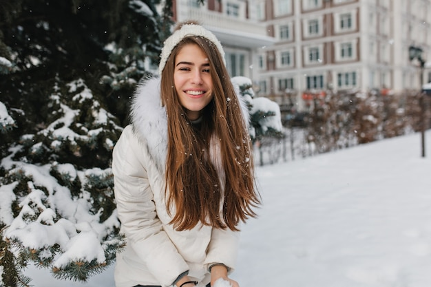Feliz invierno de mujer bonita positiva jugando con nieve. mujer sonriente con cabello largo morena disfrutando de fin de semana durante caminar por la calle en día helado.