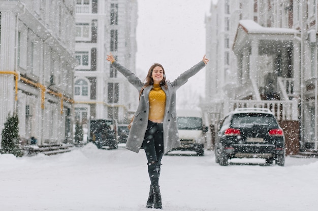 Feliz invierno nevando en la gran ciudad de la chica guapa disfrutando de las nevadas en la calle. verdaderas emociones positivas, tomados de la mano arriba,