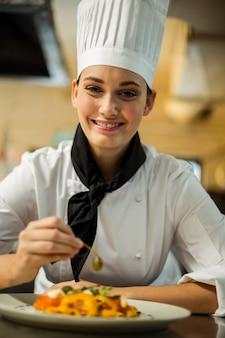 Feliz jefe de cocina adornando un plato de pasta con aceitunas