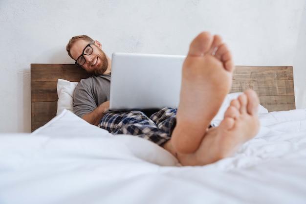 Feliz joven acostado en la cama con una computadora portátil en el estómago y sonriendo ampliamente mientras mira al frente