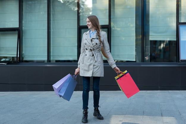 Feliz joven adicto a las compras con bolsas de colores cerca del centro comercial. caminando en la calle.