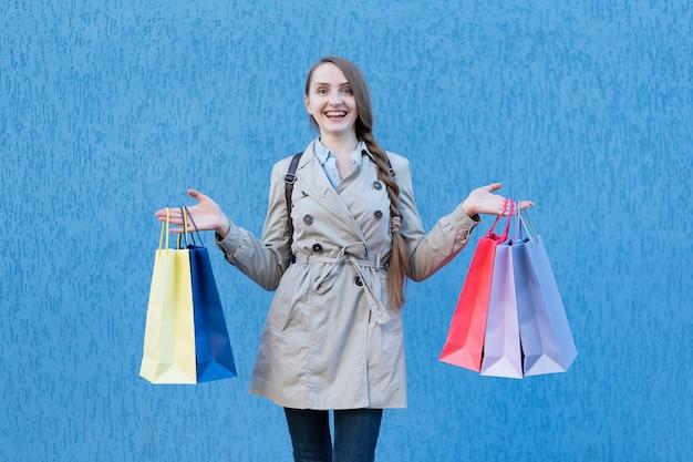 Feliz joven adicto a las compras con bolsas de colores. pared de la calle azul
