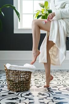 Feliz joven se afeita la pierna en la bañera