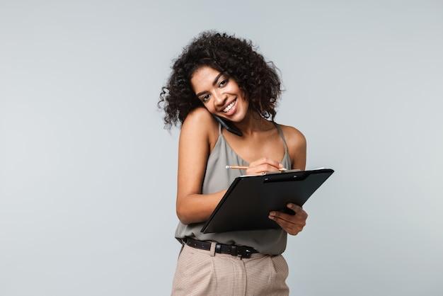 Feliz joven africana vestida casualmente que se encuentran aisladas, hablando por teléfono móvil, tomando notas