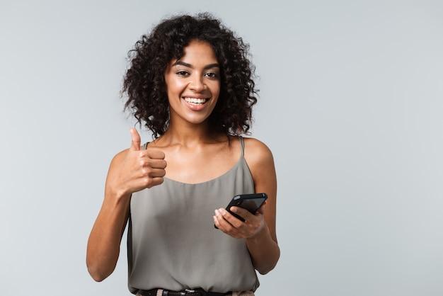 Feliz joven africana vestida casualmente que se encuentran aisladas, sosteniendo el teléfono móvil, pulgares arriba