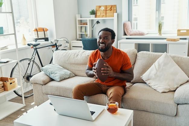 Feliz joven africano animando y sonriendo mientras ve el partido deportivo en casa