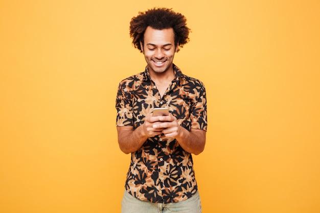 Feliz joven africano chateando por teléfono