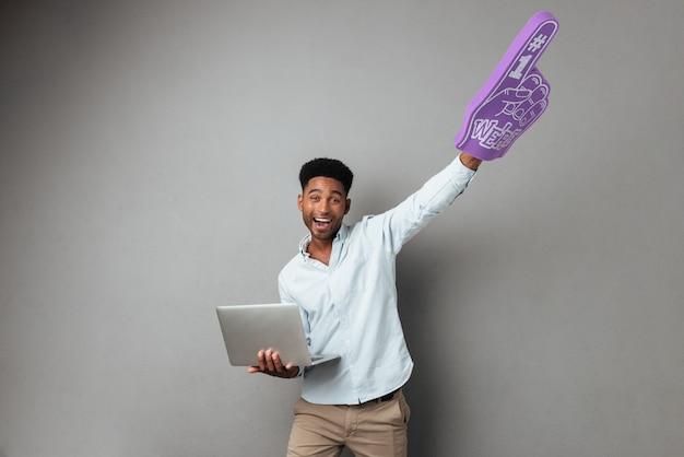 Feliz joven africano con ordenador portátil y dedo de espuma