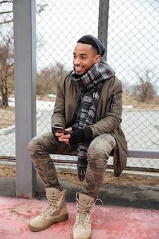 Feliz joven africano con teléfono celular al aire libre en otoño