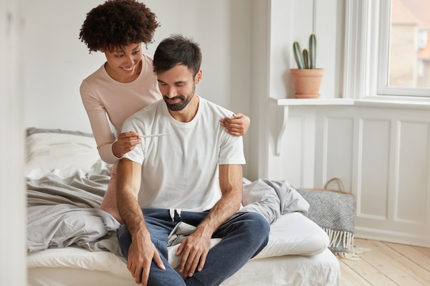 Feliz joven afroamericana muestra prueba de embarazo positiva a su marido