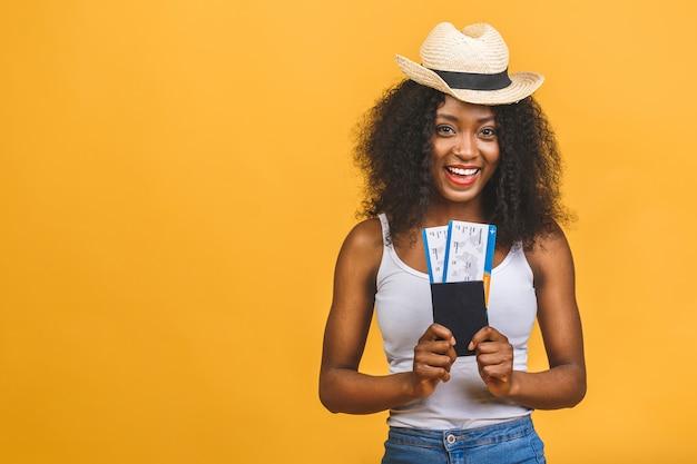 Feliz joven afroamericana negra con billetes de avión
