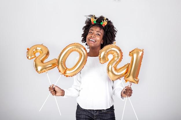 Feliz joven afroamericana sosteniendo 2021 globos de color oro para celebrar